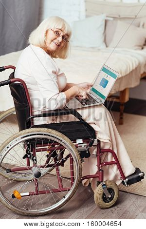 In a good mood. Delighted elderly disabled woman smiling and using laptop while sitting in the wheelchair