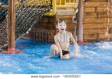 happy child in a small wading pool, looking up at the camera and smiling.