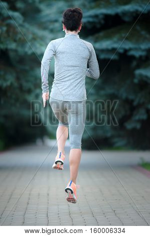 Running training runners jogging on road outside in rear view running away from camera outdoors. Sport fitness and healthy lifestyle concept