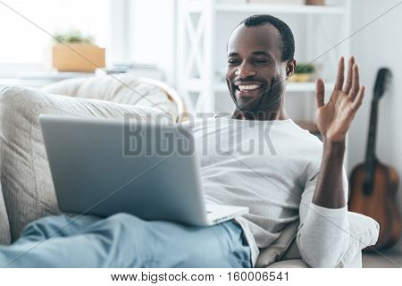 Enjoying carefree time at home. Handsome young African man looking at laptop and waving with his hand while lying on the sofa at home