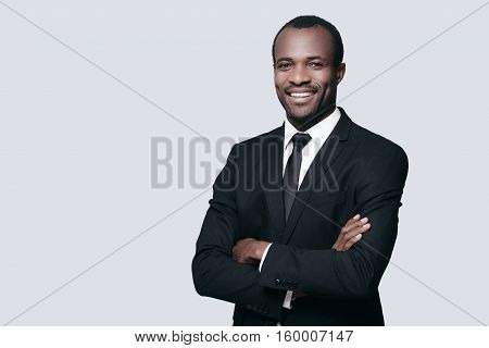 Confidence and style. Handsome young African man in formalwear keeping arms crossed and looking at camera while standing against grey background