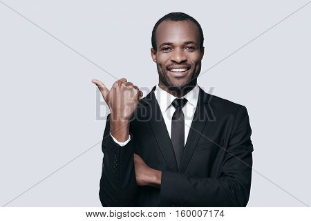 Successful choice. Handsome young African man in formalwear pointing away and smiling while standing against grey background