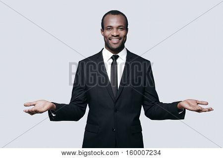 Open to new deals. Handsome young African man in formalwear gesturing and looking at camera while standing against grey background