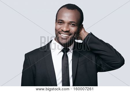 Handsome businessman. Portrait of confident young African man holding hand behind head and smiling while standing against grey background