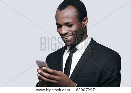 High time to chat. Handsome young African man typing message and smiling while standing against grey background
