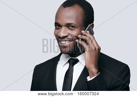 Feeling happy. Handsome young African man smiling and talking on the phone while standing against grey background