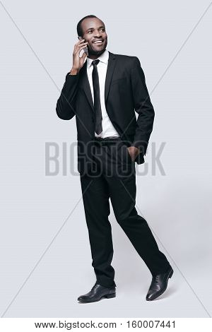 Successful businessman. Full length of handsome young African man talking on the phone and smiling while standing against grey background