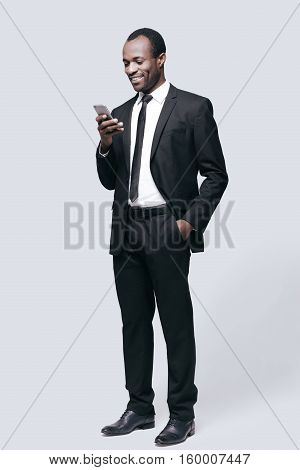Reading nice message! Full length of handsome young African man looking at mobile phone and smiling while standing against grey background