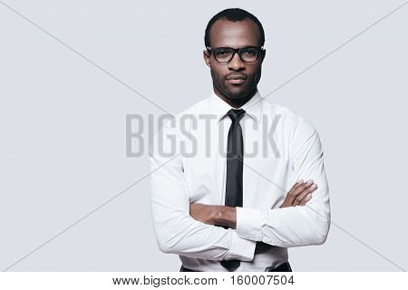 Young and successful. Handsome African man looking at camera and keeping arms crossed while standing against grey background
