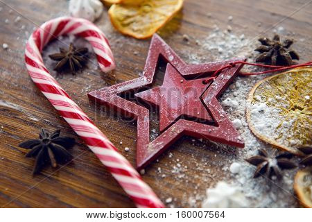 red wooden star lies with dried orange, cinnamon and meringue on wooden dark table