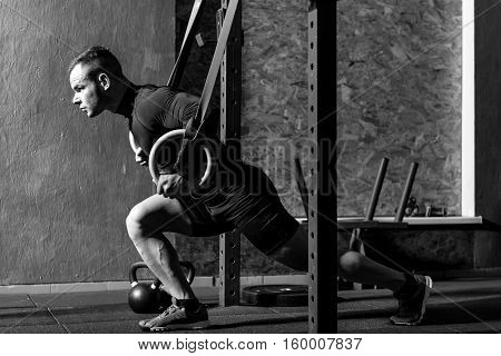 Thinking about body. Healthy well built sporty man holding gymnastic rings and doing a physical exercise while developing hid body