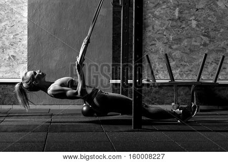Physical training. Beautiful good looking slim woman holding gymnastic rings and leaning backwards while doing a physical exercise in the gym