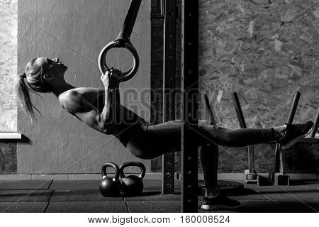 Exercises with gymnastic rings. Nice young attractive woman leaning backwards and holding one leg up while using gymnastic rings