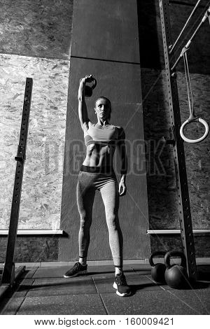 Exercising with kettlebells. Well built hard working young woman holding her hand up and lifting a kettlebell while doing a physical exercise
