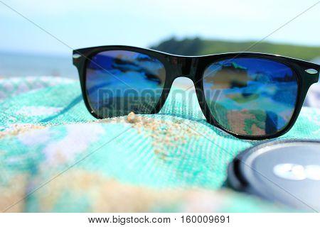Blue sunglasses on the beach where a lot of sand