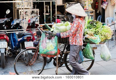 Vietnam, Hue - October 21, 2016: Vietnamese woman and bicycle with fruits and vegetables on the street in Hue, Vietnam