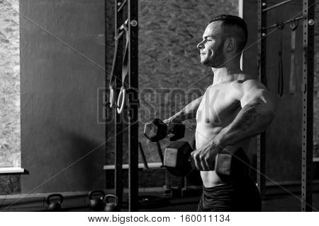 Lifting weight. Muscular well built tattooed man standing in the gym and lifting dumbbells while developing his strength