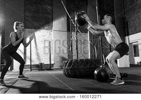 Active sport. Handsome sporty good looking man standing against his workout partner and throwing a med ball while standing in a special position