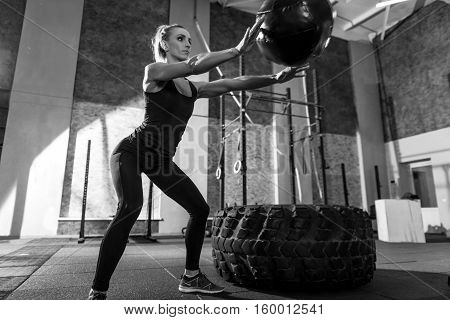 Active workout. Sporty nice attractive woman standing in a special position and holding arms in front of her while throwing a med ball