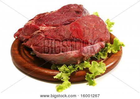 red raw beef meat and salad over white on wooden plate