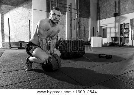 Moment of rest. Serious athletic good looking man squatting and putting a med ball on the floor while having a small relaxation during the workout
