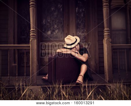 Woman sitting on threshold of old house.