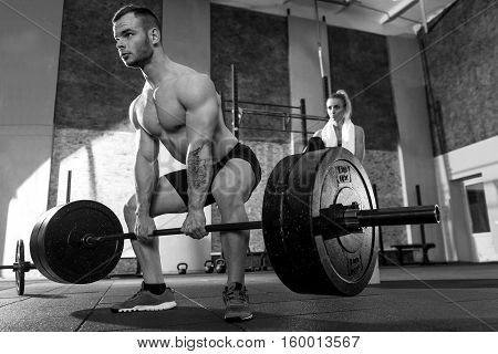 Physical strength. Brutal handsome sporty man lifting a barbell and focusing on this activity while building up his strength