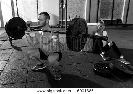 I can do it. Serious strong good looking man squatting and holding a big metal barbell while being looked at by his female workout partner