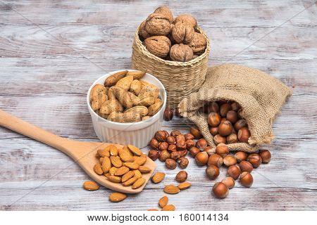 Set Of Nuts: Hazelnuts, Walnuts, Almonds On Gray Wooden Background