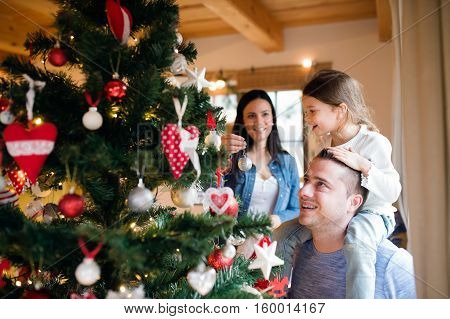 Beautiful young family with little girl decorating Christmas tree at home. Father giving daughter piggyback.