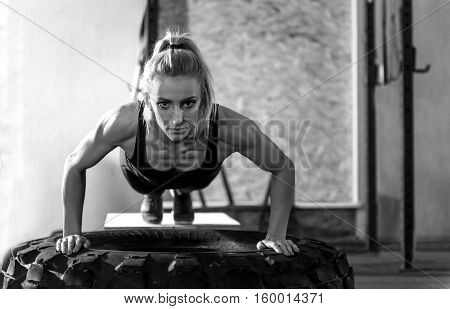 Doing push ups. Muscular well built serious woman doing push ups on a giant tire and looking at you while having an intensive workout
