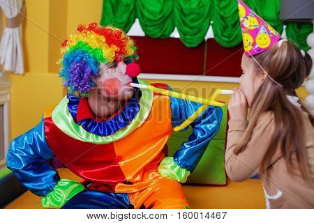 Clown and girl plays with tube on birthday party.