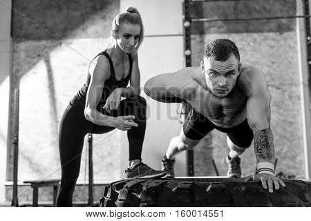 Workout partners. Nice pleasant good looking woman looking at the man and counting the amount of his push ups while working out in the gym