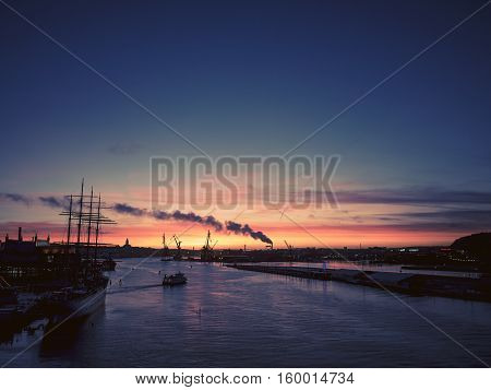 Sun setting over Gothenburg city harbor in Sweden. Shot on a beautiful autumn evening.