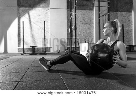 Doing physical exercises. Nice slim well built woman sitting on the floor and holding a medicine ball while doing physical exercises with it