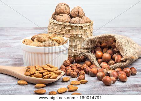 Hazelnuts, Walnuts, Almonds On Gray Wooden Background