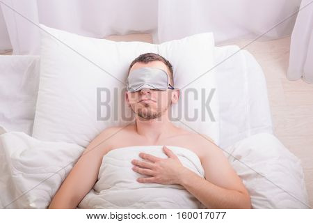 Sleeping young man in sleep mask on bed.