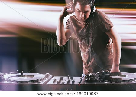 Club DJ with afro hairstyle playing mixing music on vinyl turntable at party wearing sunglasses with lens flare from nightlife lights