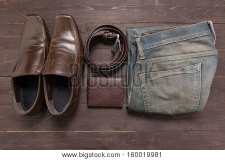 Elegant Set: Brown Wallet, Brown Men's Shoes, Brown Leather Belt, Jean On The Wooden Background