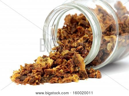 Propolis granules poured out of the jar. Isolated on white background. Apitherapy