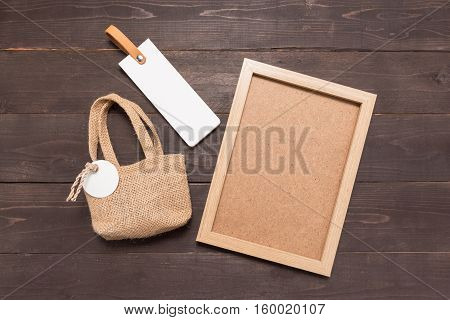 Hessian Sack Bag With Tag And Picture Frame Are On The Wooden Background