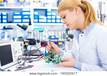 Engineer working with circuits. A woman engineer solders circuits sitting at a table.  Microchip production factory. Assembling the PCB board.  Girl repairing electronic device on the circuit board.