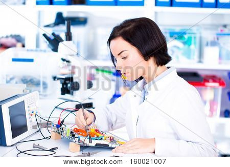 Engineer working with circuits. A woman engineer solders circuits sitting at a table.  Microchip production factory. Technological process.  Girl repairing electronic device on the circuit board.