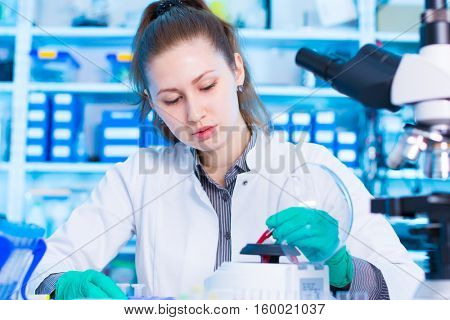woman in a laboratory with microtube test tube in hand and PCR centrifuge. scientist using a centrifuge in a laboratory