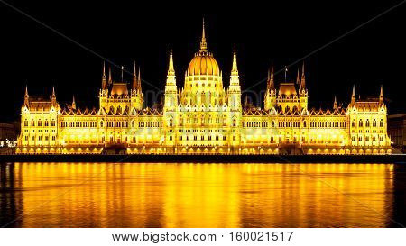 Night panoramic view of illuminated historical building of Hungarian Parliament, aka Orszaghaz, reflected in the water with typical symmetrical architecture and central dome on Danube River embankment in Budapest, Hungary, Europe. It is notable landmark a