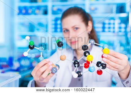 Woman scientist holding model of molecule or crystal lattice. scientist working at the laboratory. Model of molecule on a table