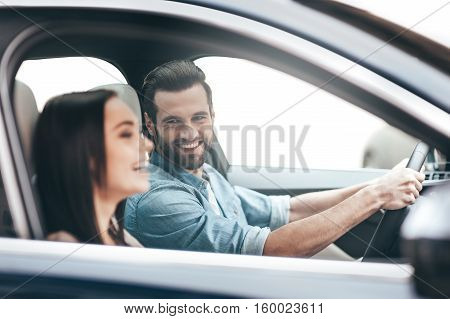 Enjoying the trip. Young couple sitting in the car and smiling while handsome man holding hands on the steering wheel