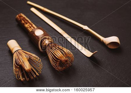 Two chasens - special bamboo whisk and two bamboo spoons for matcha tea. Special accessories for japanese matcha, lying on black textured stone background.
