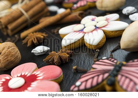 Gingerbread cookies with nuts and spices, colorful homemade cakes in shape of flower and butterfly on black textured background, selective focus
