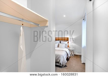 Bedroom entrance with white walls and dress hanger next to sleeping room window with a lamp and bedding